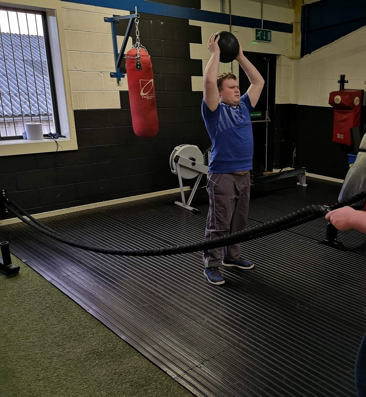 Young man lifting weights in a gym
