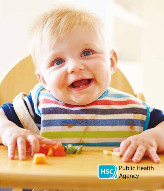 Baby in high chair eating pieces of fruit