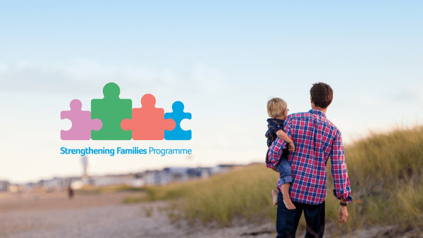 Strengthening Families logo with the background of a man carrying his son on a beach