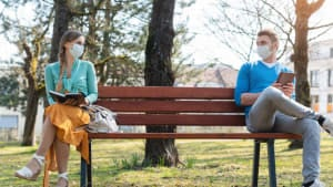 young woman and young man with masks and social distancing on park bench
