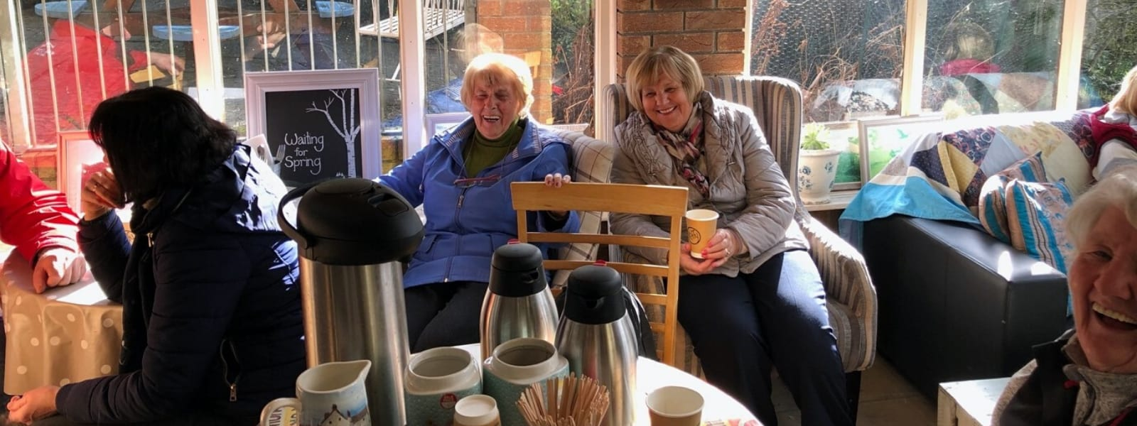 Two women sitting in chairs enjoying a cup of tea together