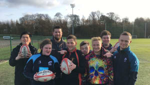 Group of 7 young people and their coach holding rugby balls