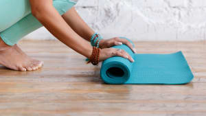 partial image of lady unrolling yoga mat